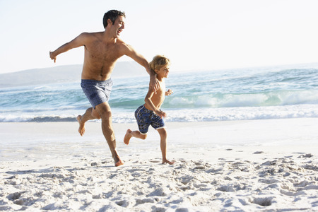 swimming costumes: Father And Son Running Along Beach Together Wearing Swimming Costumes