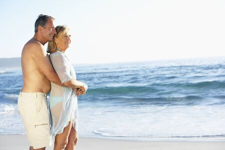 board shorts: Senior Couple On Holiday Running Along Sandy Beach Looking Out To Sea Stock Photo