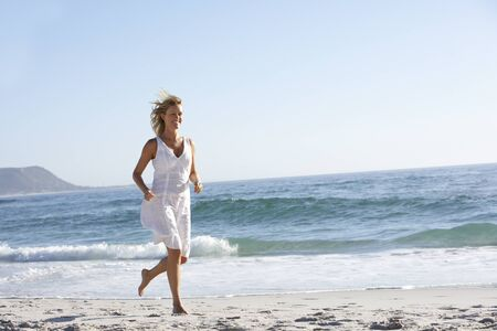 mid thirties: Casually Dressed  Young Woman Running Along Beach
