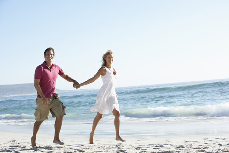 causal clothing: Young Couple Walking Along Sandy Beach On Holiday Stock Photo
