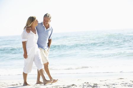 Couple supérieurs le temps des fêtes en marche le long de la plage de Sandy
