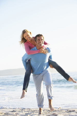 Man Giving Woman Piggyback On Beach Stock fotó