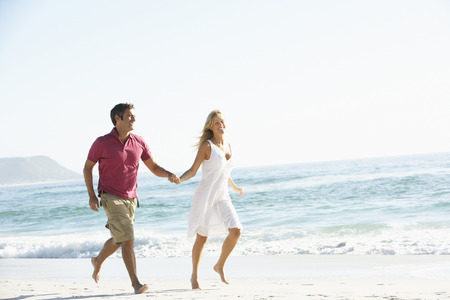 mid thirties: Young Couple Running Along Sandy Beach On Holiday Stock Photo