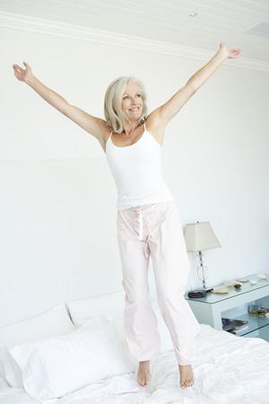 persona saltando: Mujer mayor que salta en cama