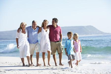 familia de cinco: Familia de tres generaciones recorre a lo largo de la playa Foto de archivo