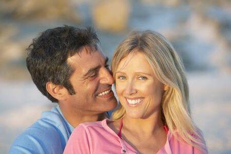 causal clothing: Romantic Young Couple Sitting On Beach
