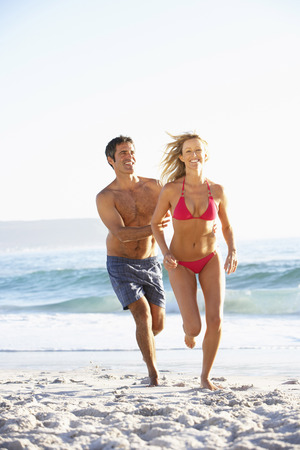 board shorts: Young Couple Running Along Sandy Beach on Holiday