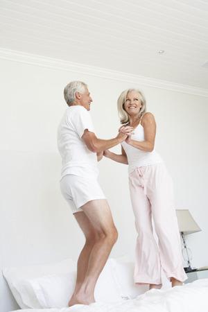 persona saltando: Pareja mayor que salta en la cama vistiendo pijamas Foto de archivo