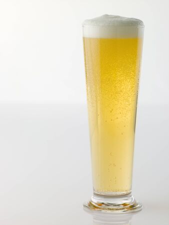 foaming: Glass Of Foaming Beer On White Background Stock Photo