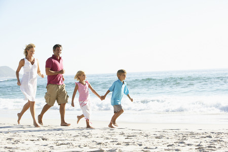 Young Family Running Along Sandy Beach On Holiday Stockfoto