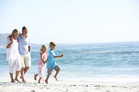 祖父母と孫のビーチに沿って歩く