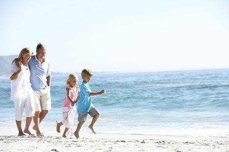 Les grands-parents et petits-enfants marchant le long de la plage Banque d'images