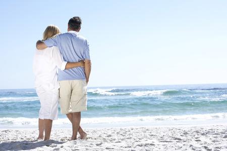 Senior Couple en vacances marchant le long de la plage de sable face à la mer