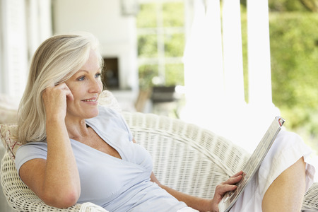 read magazine: Senior woman reading outside Stock Photo
