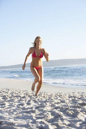 causal clothing: Young Woman Running Along Sandy Beach On Holiday Wearing Bikini