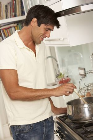 cooker: Man Preparing Meal At Cooker
