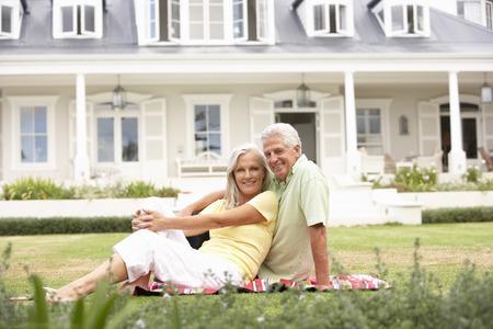 祖父母と孫の家の外の芝生の上に座っています。