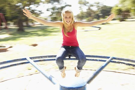 teenagers laughing: Teenager Girl Sitting On Playground Roundabout