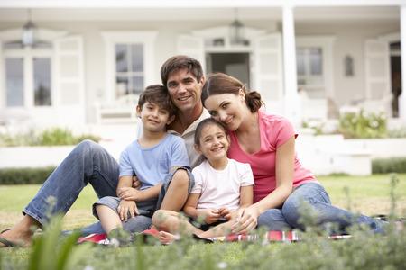 잔디밭에 집 밖에 앉아 가족