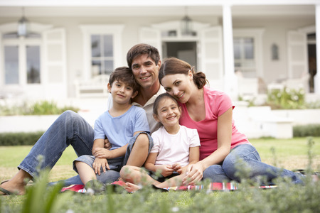 home garden: Family Sitting Outside House On Lawn