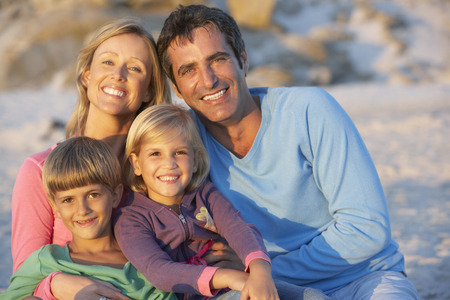 mid thirties: Portrait Of Young Family Sitting On Beach
