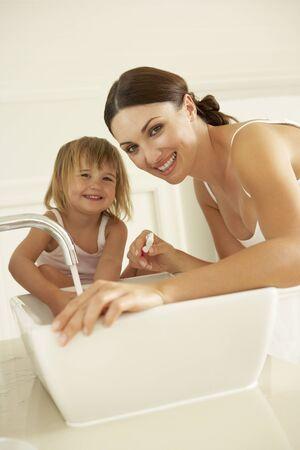 hygeine: Mother And Daughter Brushing Teeth In Bathroom