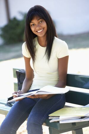 revision book: Female College Student Sitting On Bench With Book