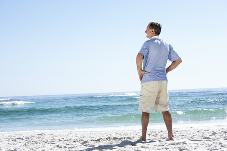 man looking out: Senior Man On Holiday Standing On Sandy Beach Stock Photo
