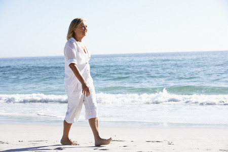 baby boomer: Senior Woman Walking along Sandy Beach