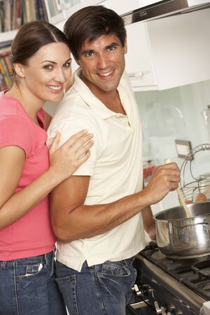 cooker: Couple Preparing Meal At Cooker