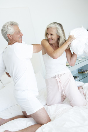 mature couples: Senior Couple in bedroom having pillow fight