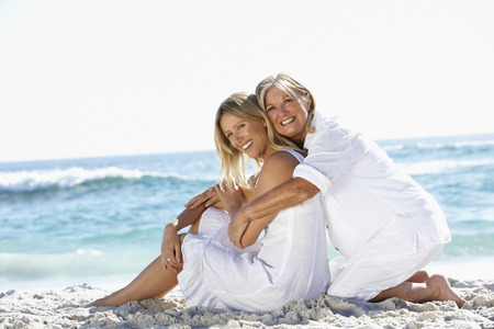 causal clothing: Mother And Adult Daughter Sitting Together On Beach Stock Photo