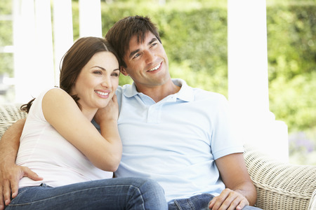 cane sofa: Young Couple Relaxing On Cane Sofa At Home