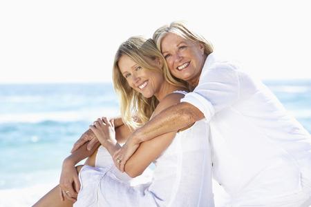Moeder en volwassen dochter zitten samen op het strand Stockfoto