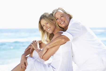 daughter mother: Mother And Adult Daughter Sitting Together On Beach Stock Photo