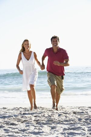 causal clothing: Couple Running Along Sandy Beach Holding Hands
