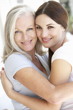 grown ups: Mature Mother And Daughter Hugging Stock Photo