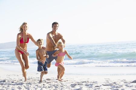 vacaciones playa: Familia de joven que se ejecuta a lo largo de la playa en vacaciones