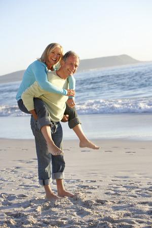 Senior pár s Piggy Bck na písečné pláži Reklamní fotografie