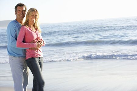 causal clothing: Young Couple Standing on Sandy Beach