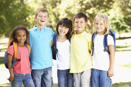 pupils: Group Of Primary School Pupils Wearing Backpacks In Park Stock Photo