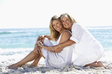 母と一緒にビーチに座って大人の娘