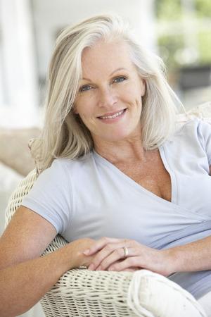 Portret van senior vrouw ontspannen in stoel Stockfoto