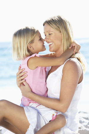 causal clothing: Mother And Daughter Sitting Together On Beach