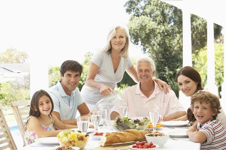 Three Generation Family Enjoying Meal Outdoors Imagens