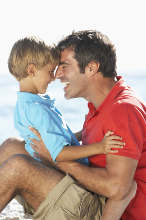 causal clothing: Father And Son Having Fun Together On Beach