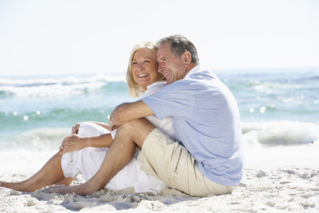 砂浜に座って休日シニア カップル
