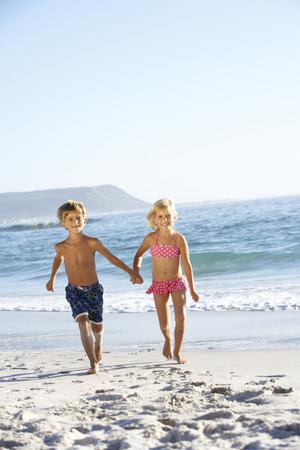 three year old: Children running along sandy beach