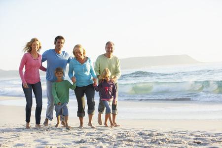 Tři generace rodiny na dovolené procházky podél pláže Reklamní fotografie