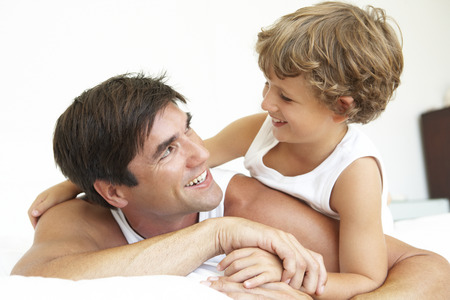 padres: Padre e hijo se relaja en la cama juntos